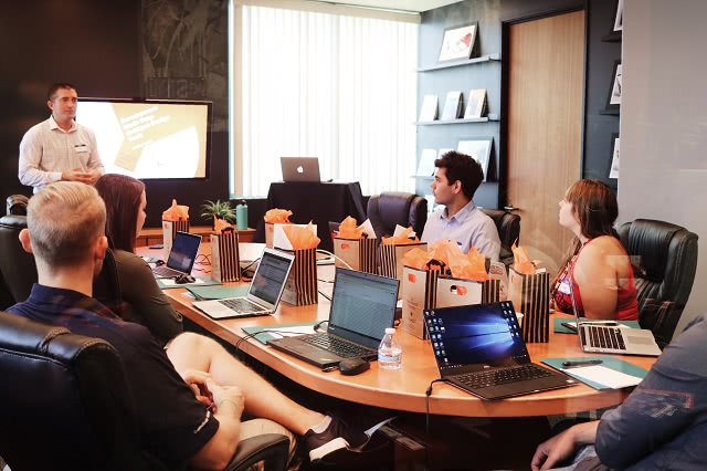 Team meeting with laptops on desk